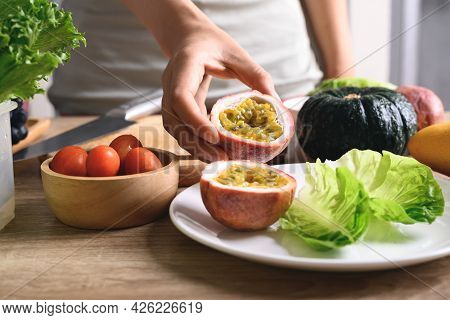 Hand Of Woman Holding Sliced Passion Fruit And Preparing Vegetables For Vegan Food Cooking On Wooden