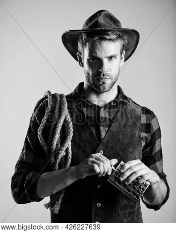 Western Life. Sheriff Concept. Bourbon Whiskey. Western Culture. Man Wearing Hat Hold Rope And Flask