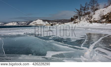 There Are Deep Cracks On The Ice, A Little Snow. In The Distance, A Blue, Non-freezing River Is Visi