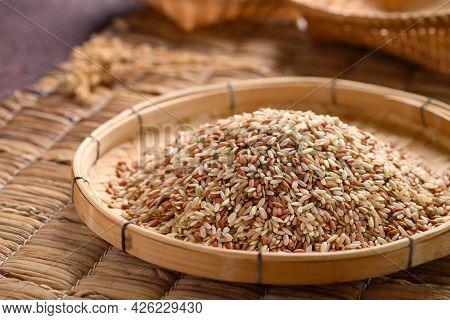 Organic Thai Highland Brown Rice Grain In A Bamboo Basket (cargo Rice, Loonzain Rice Or Husked Rice)