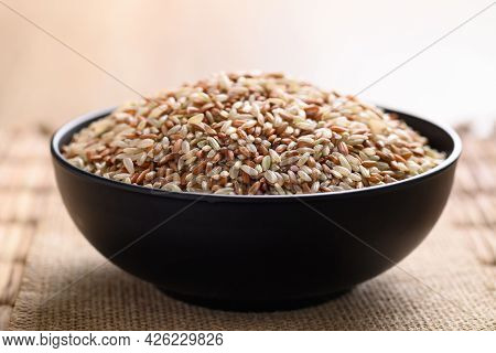 Organic Thai Highland Brown Rice Grain In A Bowl (cargo Rice, Loonzain Rice Or Husked Rice), Healthy