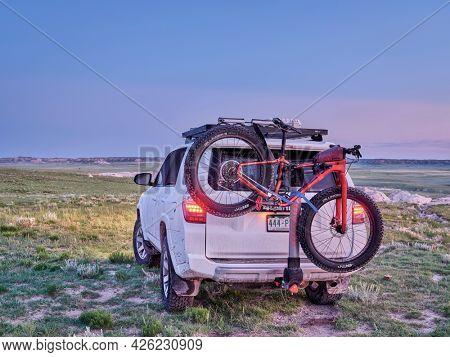 Pawnee National Grassland, CO, USA - June 2, 2021: Toyota 4Runner SUV with Salsa Mukluk fat bike on Yakima hitch rack at dawn in a prairie in northern Colorado.