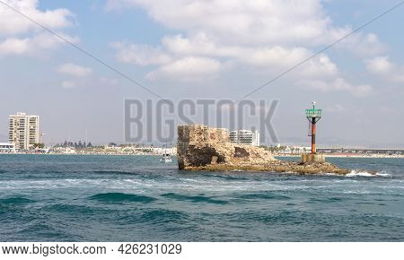 Acre, Israel, June 26, 2021 : Remains Of The Fortress Wall And A Lighthouse On It In The Mediterrane