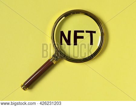 Nft Acronym Through Magnifier On Yellow Background.