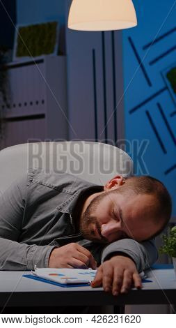 Exhausted Overworked Businessman Sleeping On Desk Table In Startup Business Office After Analysing F