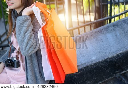 Cropped Shot View Of Young Woman Holding Spunbond Shopping Bags In Her Hands After Shopping. Spunbon