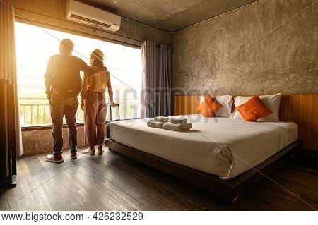 Portrait Of Young Couple Tourist Standing Nearly Window, Looking To Beautiful View Outside In Hotel/