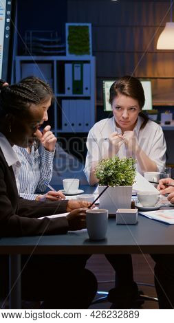 Diverse Multiethnic Business Teamwork Overworking In Office Meeting Room Analyzing Financial Graphs