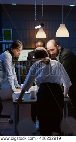 Multi Ethnic Businesspeople Teamwork Standing At Conference Table Analyzing Management Graphs In Eve
