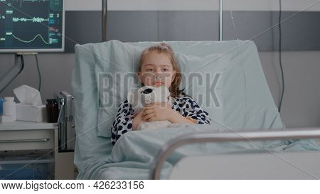 Portrait Of Lonley Sick Little Child Resting In Bed Holding Teedy Bear In Hands Looking At Camera Du
