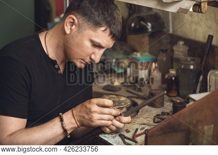 The Jeweler Inspects The Gold Ring For Defects In His Workshop