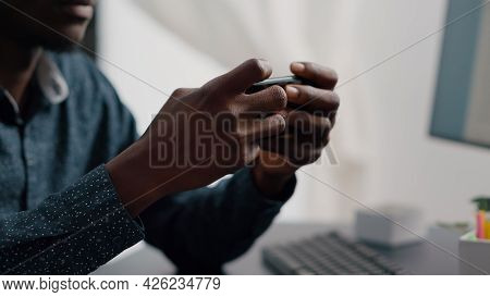 Close Up Of Black Man Hands Playing Online Internet Mobile Video Games On His Phone At Home. Leisure