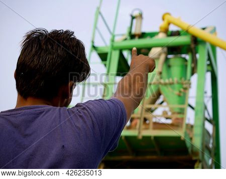 An Indian Male Worker Pointing Finger Towards Concrete Mixer Machine Around Sky Industrial Backgroun