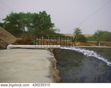 Water Force Flowing With Pressure On Cement Tank At Natural Background..