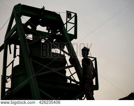 Asian Labor Working At Concrete Mixer Machine Presenting Around Sky Silhouette Industrial Background
