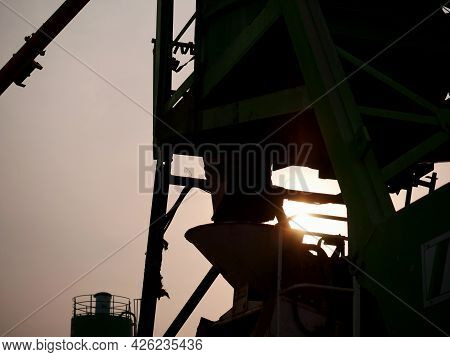 Concrete Mixer Machine Presenting With Sun Light Sky Industrial Background.