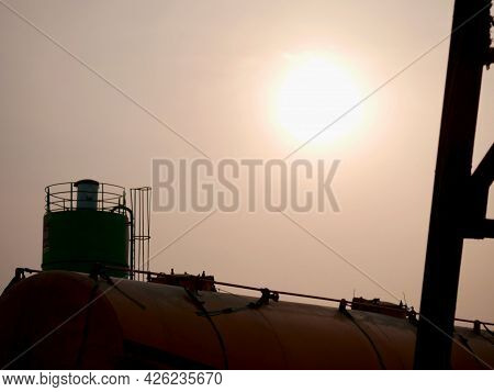Oil Container With Concrete Mixer Presenting Around Sky Industrial Background.