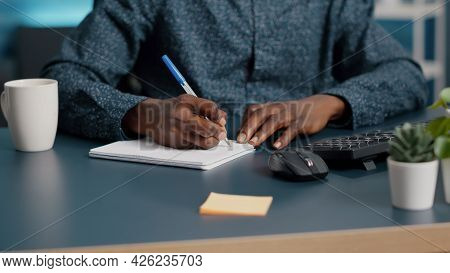 Closeup African American Black Man Hands Taking Notes On Notepad Using A Pen. Male Adult Hands Of Re