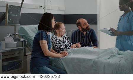 African American Pediatric Asisstant Monitoring Sick Child Discussing Recovery Treatment With Parent