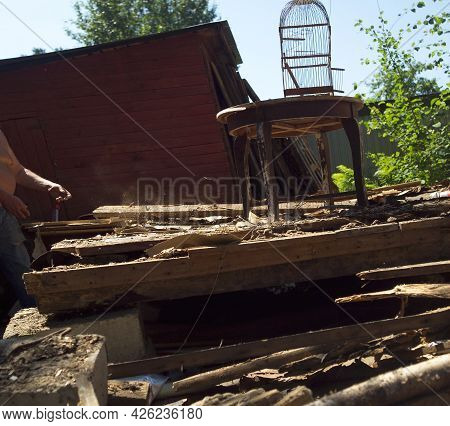 A Worker Sorting Through The Rubble Of Destrcuted House, Summertime Outdoor Shot