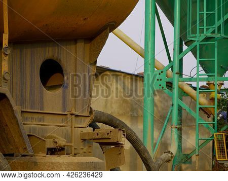 Concrete Mixer Machine With Pipe Connection Presenting Around Sky Industrial Background.