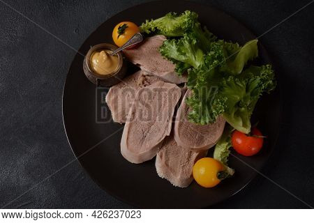 Sliced Beef Tongue Slices On A Platter With Lettuce Leaves, Cherry Tomatoes And Dijon Mustard On A B