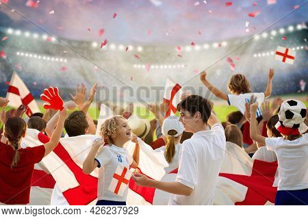England Football Supporter On Stadium. English Fans On Soccer Pitch Watching Team Play. Group Of Bri