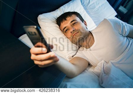 A Man Wakes Up In Bed And Looks At The Phone, Turns Off The Alarm And Looks At The Time, Surf The In