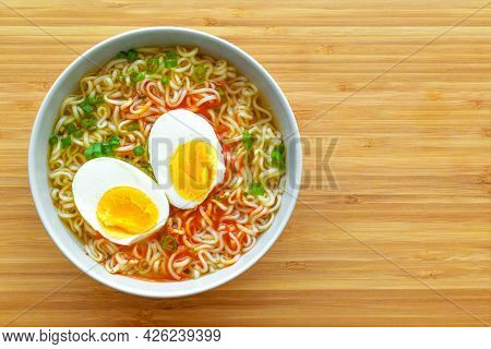 Instant Noodles With Boiled Egg And Spring Onion In A Bowl On A Bamboo Chopping Board.