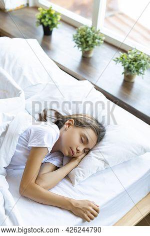 A 10-year-old Girl Sleeping Under A Blanket.