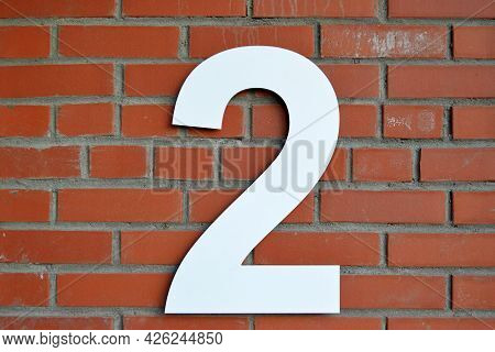 The Number 2 Is White, Isolated On A Red Brick Wall.location.street Or House Number Three.stone Text
