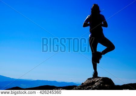 Girl on mountain top silhouette holding yoga pose for health and mental wellness