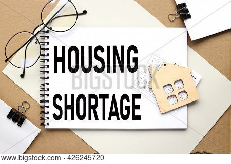Housing Shortage. The Text On The Notebook On Which The Wooden Figure Of The House Lies