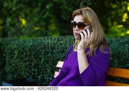 Defocus Caucasian Blond Woman Talking On The Phone Outside, Outdoor. 40s Years Old Woman In Purple B