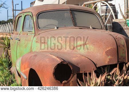 Old Rusty Car  Vintage Antique From The Fifties No Wheels On Blocks With Pot Plants Around Vehicle.