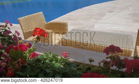 Summer Terrace With Wicker Rattan Chairs And Table Near Pool Resort. Red Geranium Flowers In Flowerb