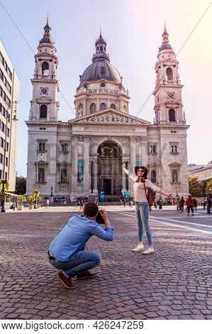 Young Couple Take Pictures Of Each Other While Standing In Front Of St. Stephens Basilica In Budapes