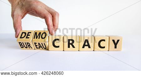 Democracy Or Bureaucracy Symbol. Businessman Turns Wooden Cubes And Changes The Word Bureaucracy To