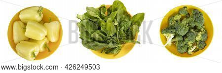 Fresh Vegetables In Yellow Bowls Isolated On A White Background. Sweet Pepper, Broccoli And Spinach