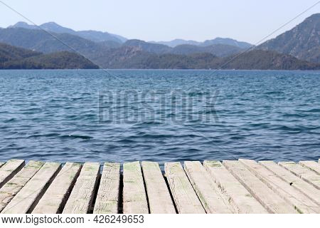 View From Old Wooden Pier To Deep Blue Water And Misty Mountains Covered With Forest. Beach Vacation