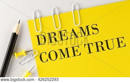 Dreams Come True Word On The Yellow Paper With Office Tools On The White Background