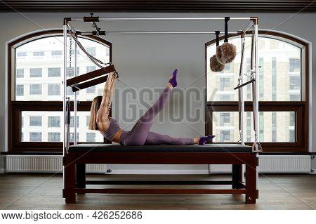 A Woman Yoga Instructor Trains On A Reformed Cadilac In A Large Hall Against A Window, Modern Equipm