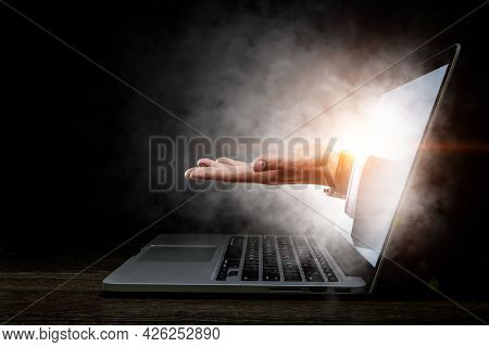 Laptop with lit screen and human open palm hand
