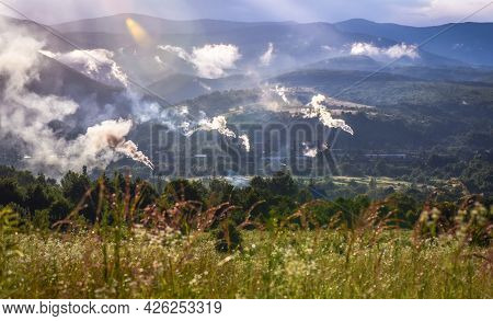 Mountain Landscape With A Working Plant After A Thunderstorm