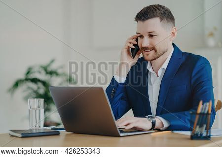 Young Successful Entrepreneur In Formal Suit Talking On Mobile Phone, Smiling And Discussing Busines