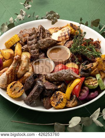 Platter With Mixed Grilled Meat And Vegetables On Green Background. Tasty Lunch. Vertical Format. So
