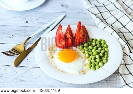 Fried Eggs With Peans And Tomatoes On A White Plate.
