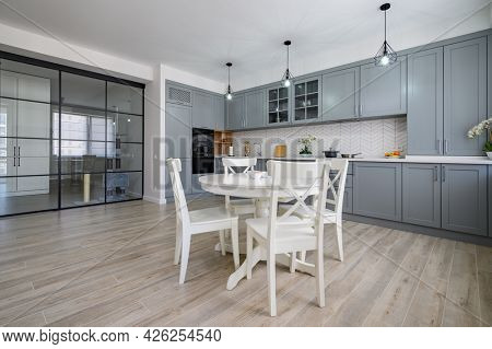 Trendy grey and white modern kitchen with white round dining table in studio apartment