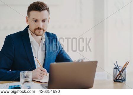 Serious Bearded Man Marketer Involved In Working Process Makes Notes With Pencil Looks Attentively A