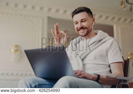 Modern Bearded Guy Makes Okay Gesture Looks Gladfully At Laptop Display Wears Earbuds Has Video Call